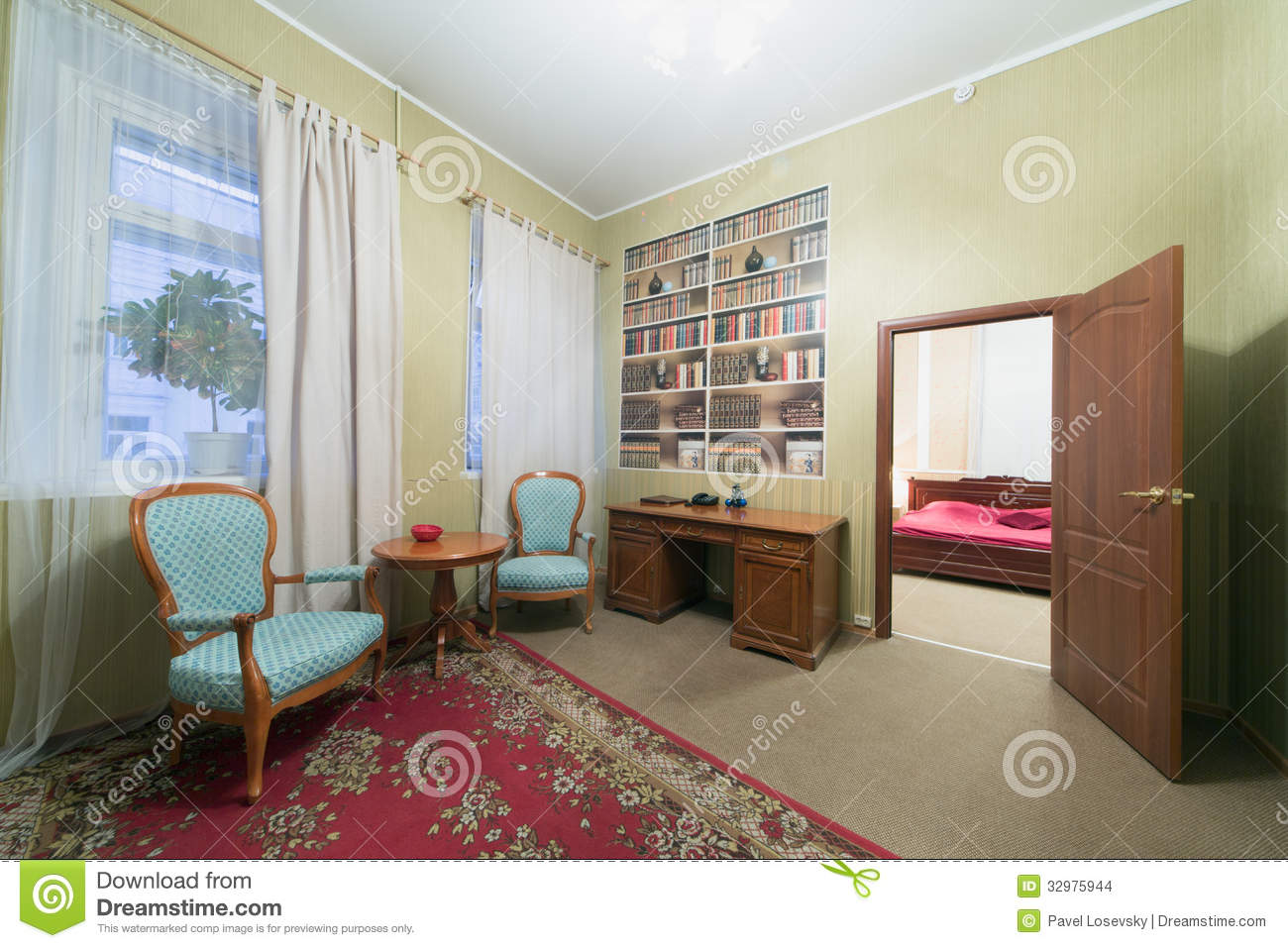 Sitting area with two chairs and an open door leading to the bedroom
