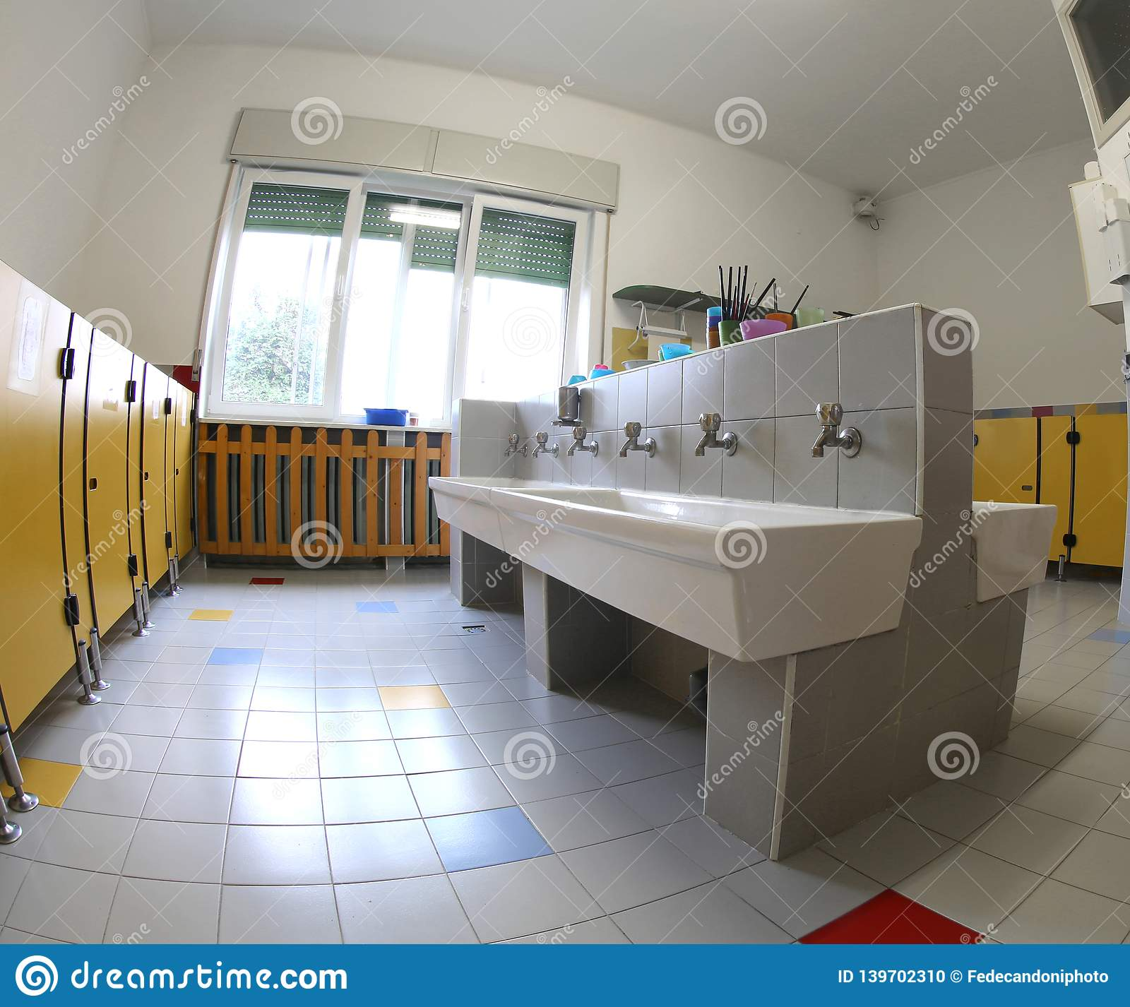 Interior of the school bathrooms with ceramic sinks and yellow d