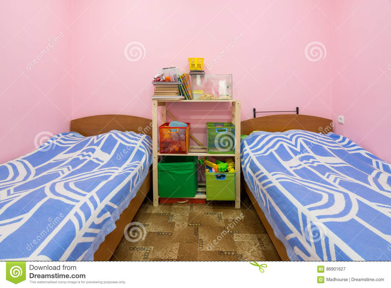 The interior of small dorm room with two beds and a homemade rack in the middle