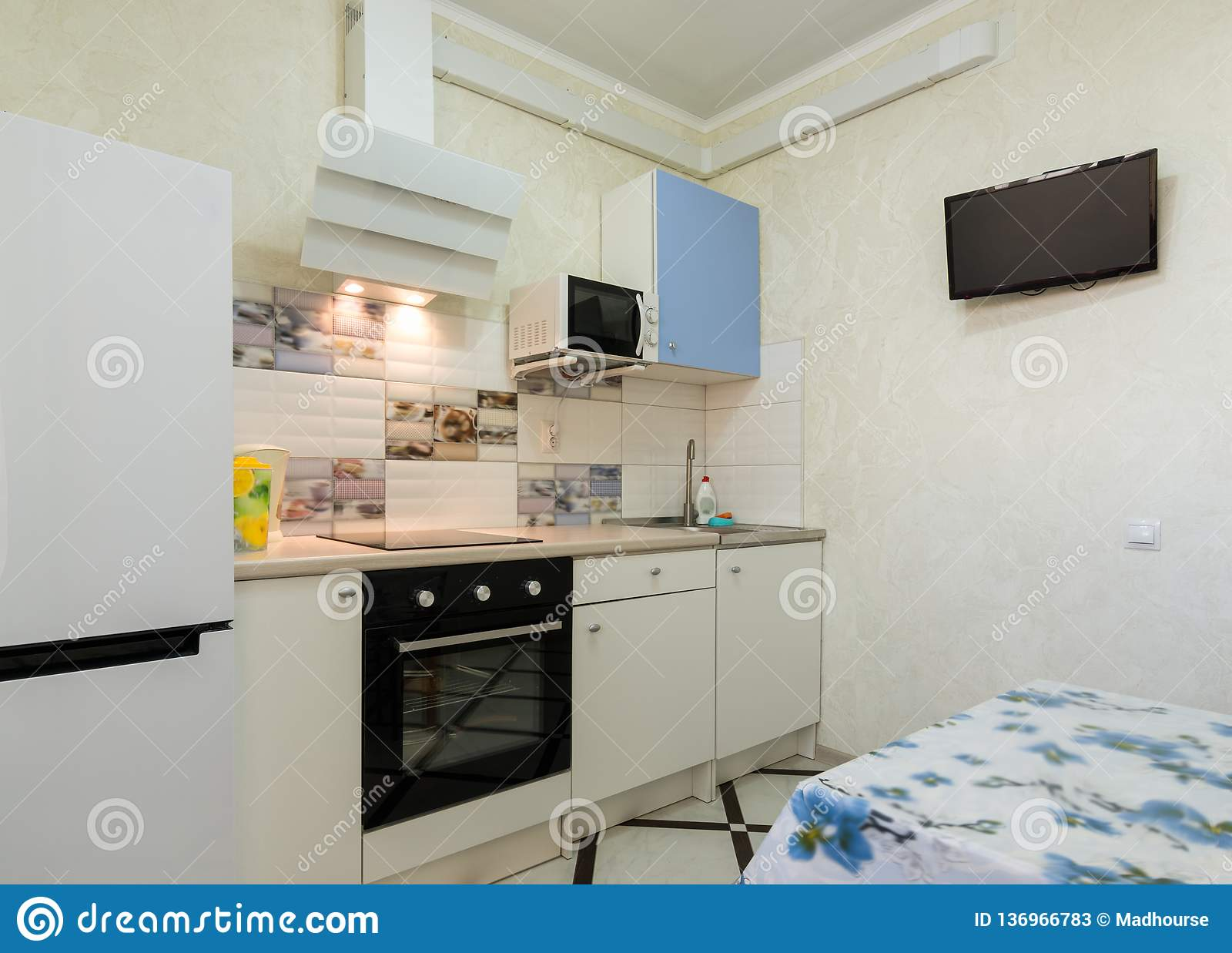 The Interior Of A Small Kitchen With A TV On The Wall Stock ...