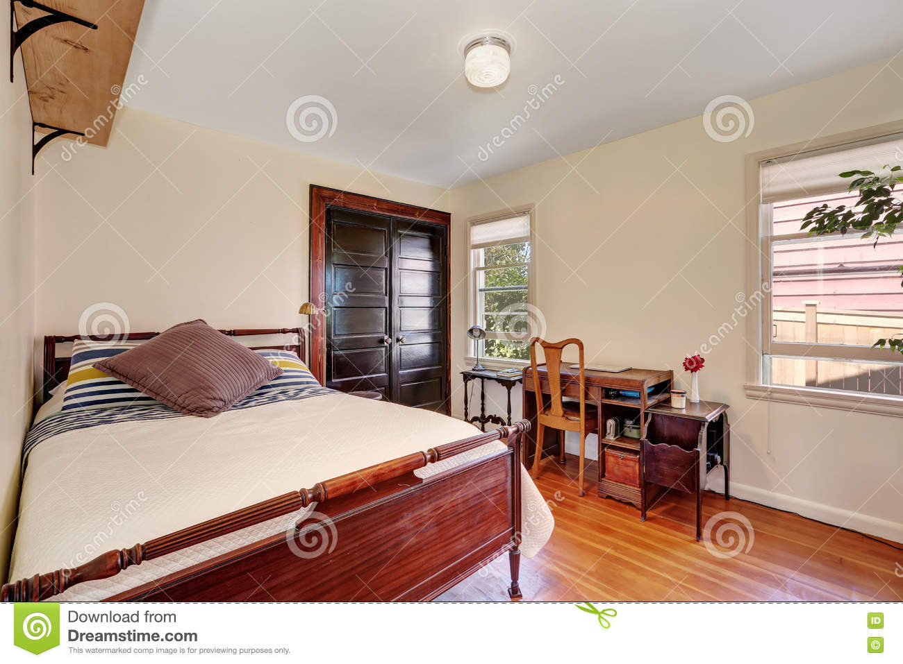 Interior of small white bedroom with vintage desk stock image