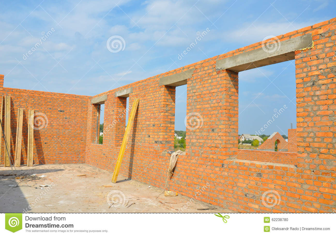 Interior of a unfinished red brick house walls under for Casas de madera infantiles para exterior