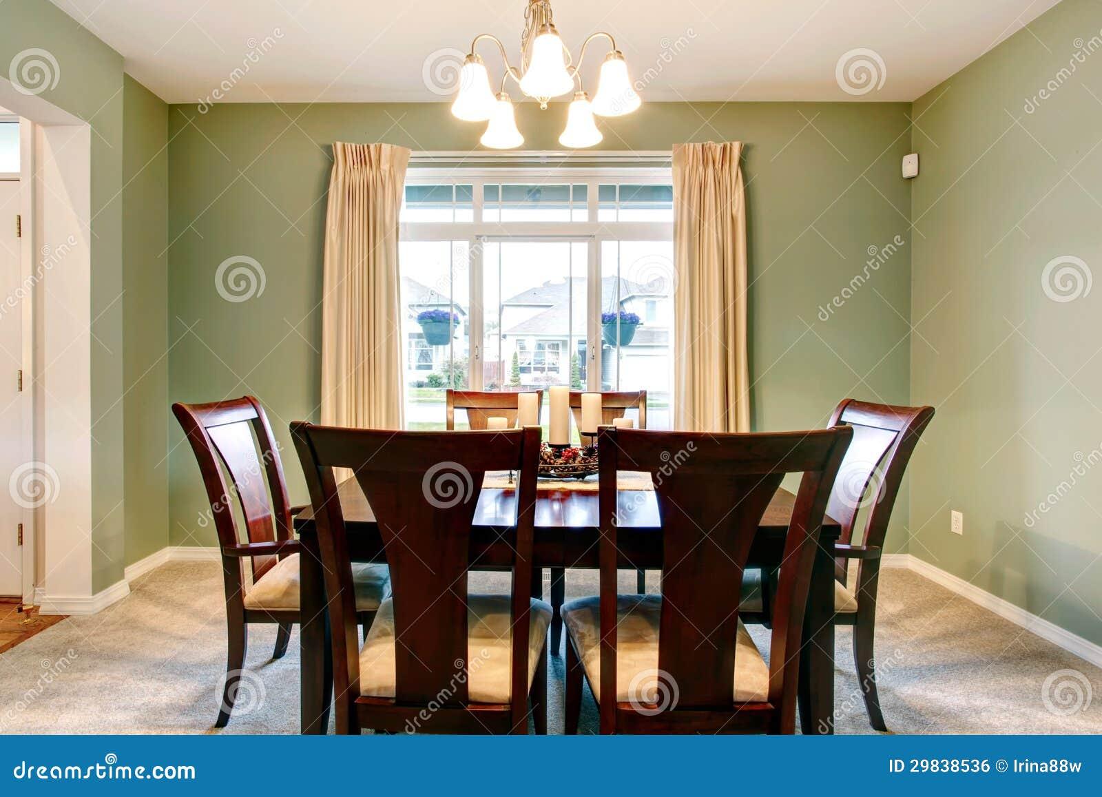 verde del comedor con muebles marrones clásicos y alfombra beige