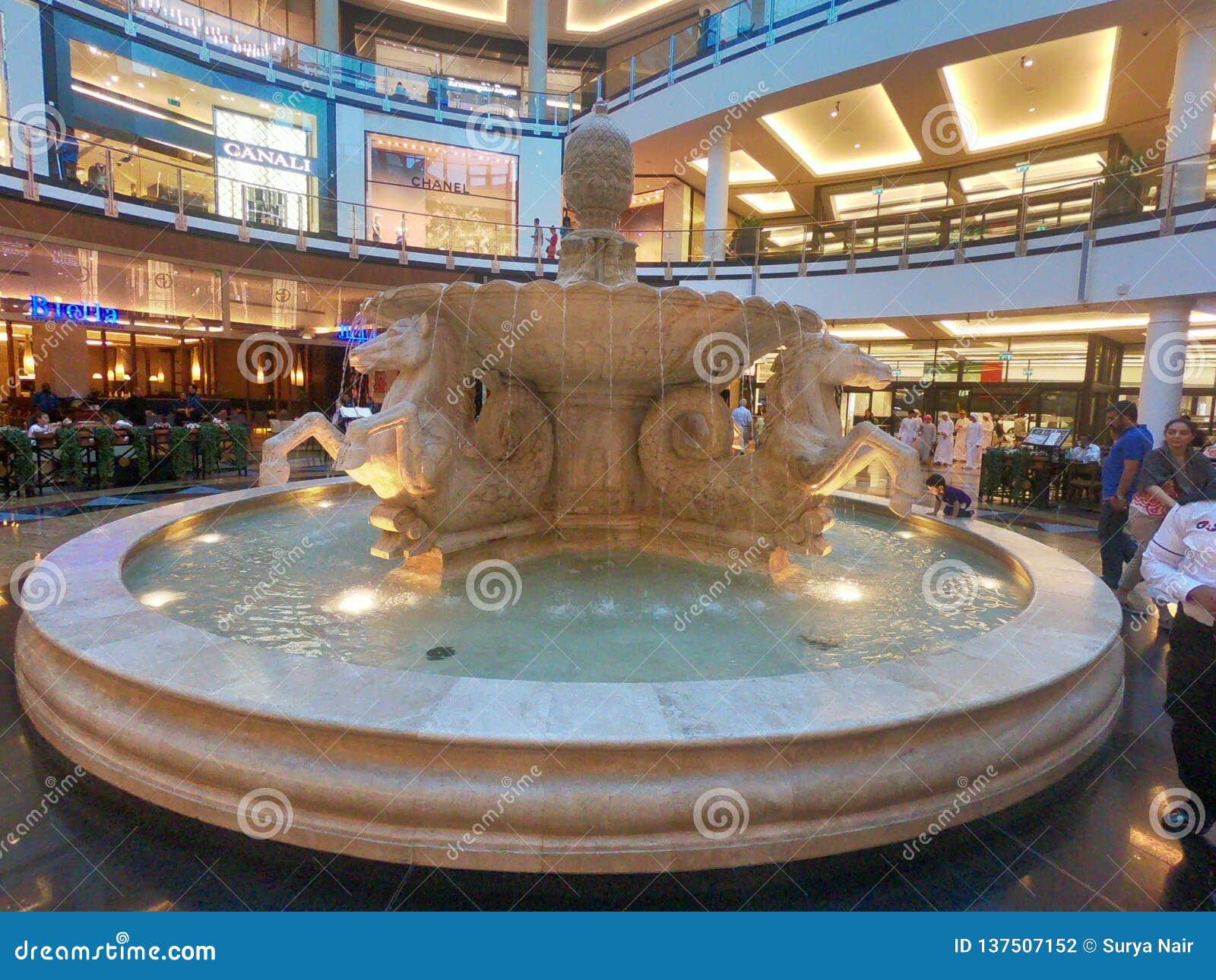 Interior View of People walking around Horses Fountain inside Mall of the Emirates located in Barsha, Dubai, United Arab Emirates