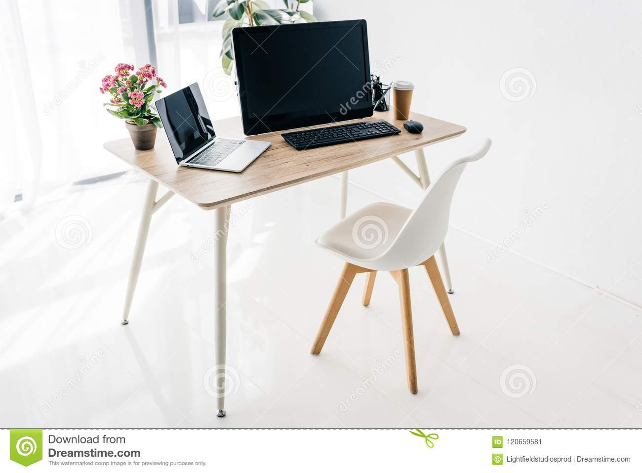 interior of workplace with chair, flowers, coffee, stationery, laptop and computer