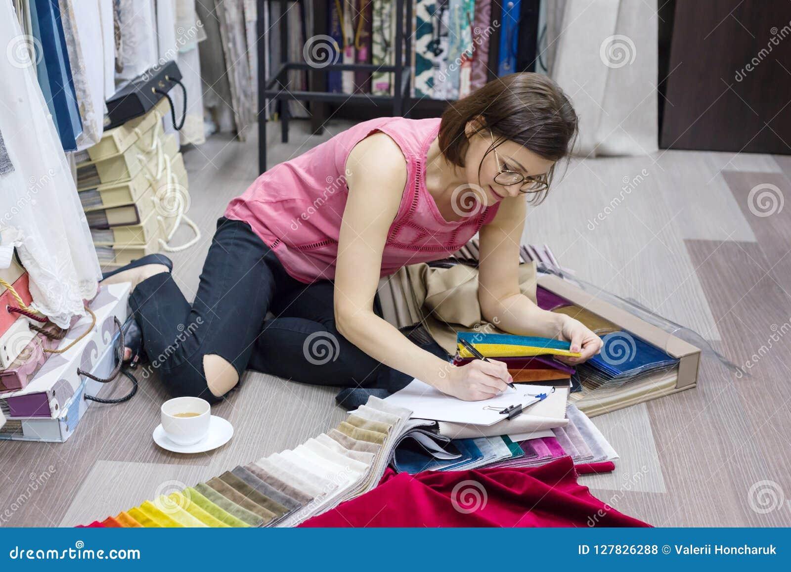 Interiorista de la mujer, trabajos con las muestras de telas para las cortinas y persianas Negocio - industria textil