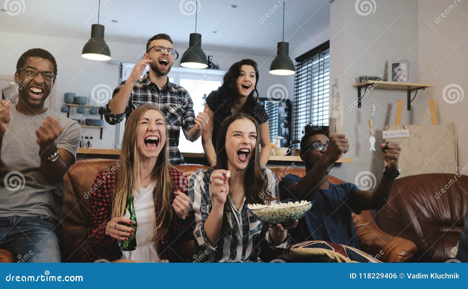 Interkulturelles Gruppenuhrsportspiel im Fernsehen Leidenschaftliche Anhänger feiern Ziel mit Getränken Abschluss der Zeitlupe-4K