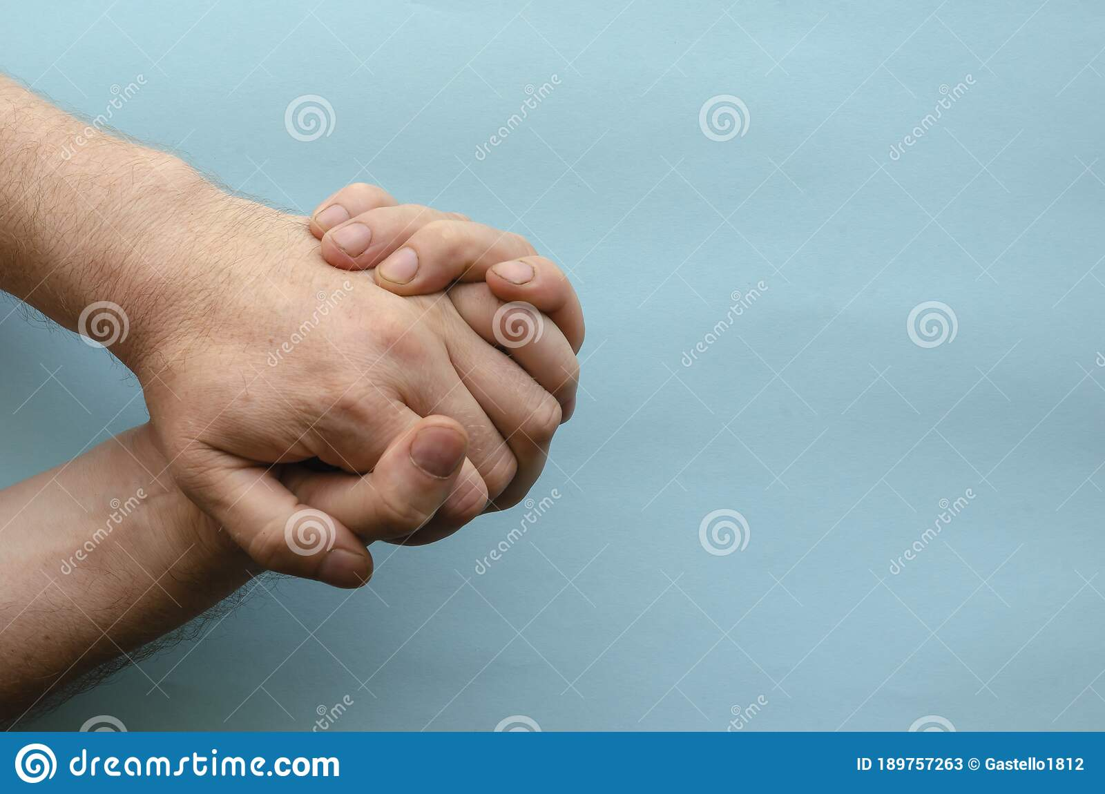 Interlocked Fingers Of Two Male Hands On Blue Background