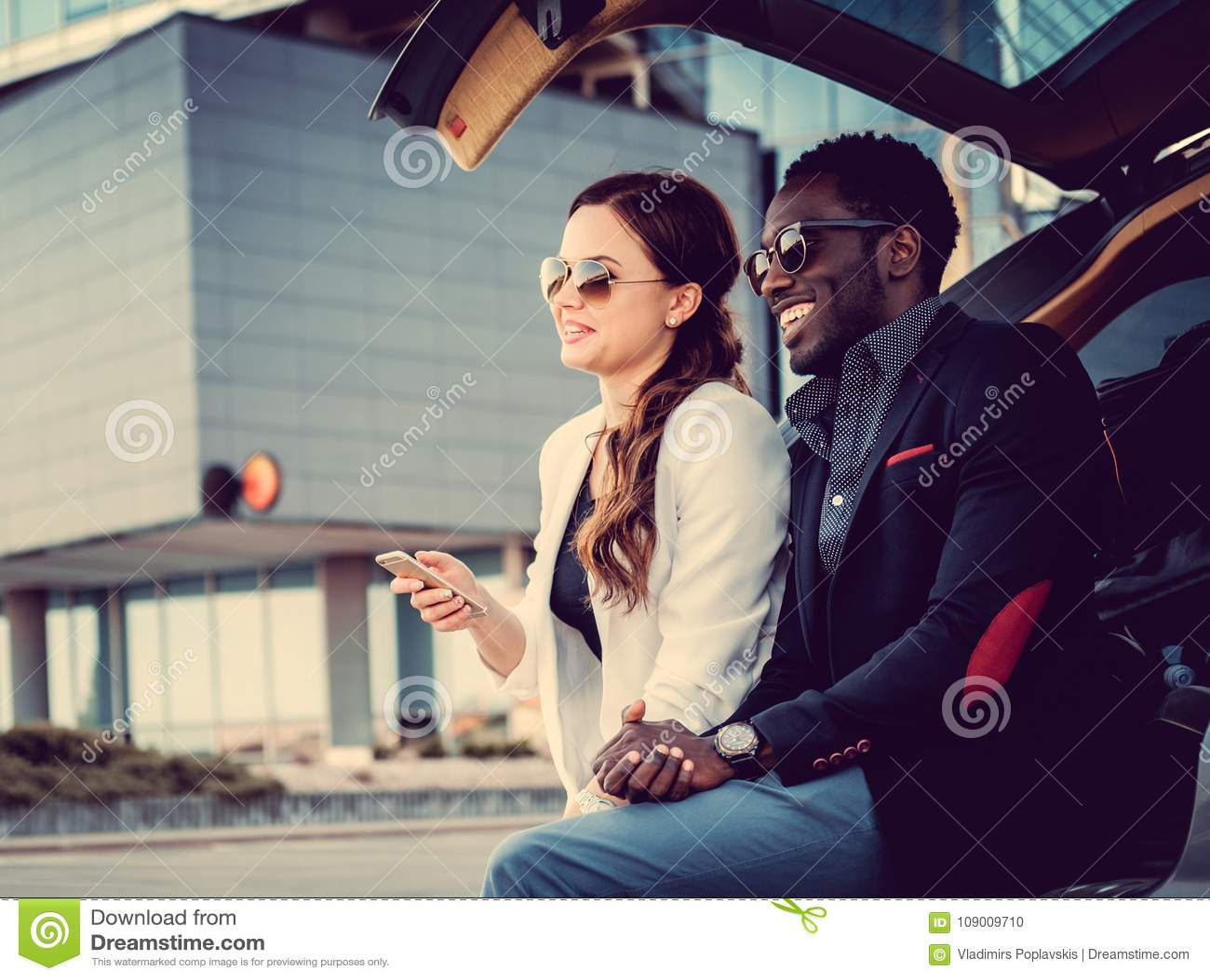 https://thumbs.dreamstime.com/z/international-couple-smartphone-near-car-international-couple-smartphone-near-car-downtown-109009710.jpg