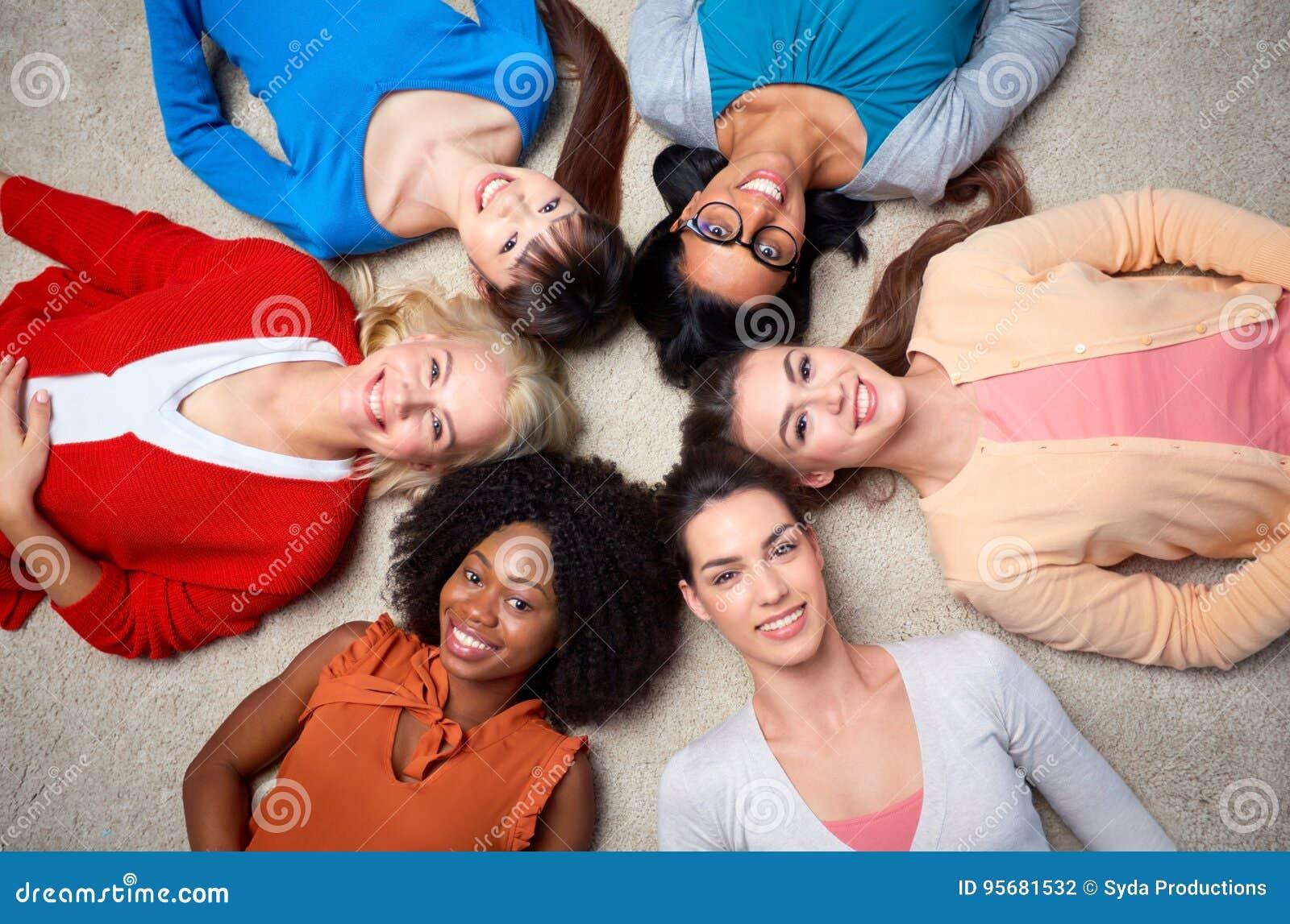 Internationell grupp av lyckliga kvinnor som ligger på golv