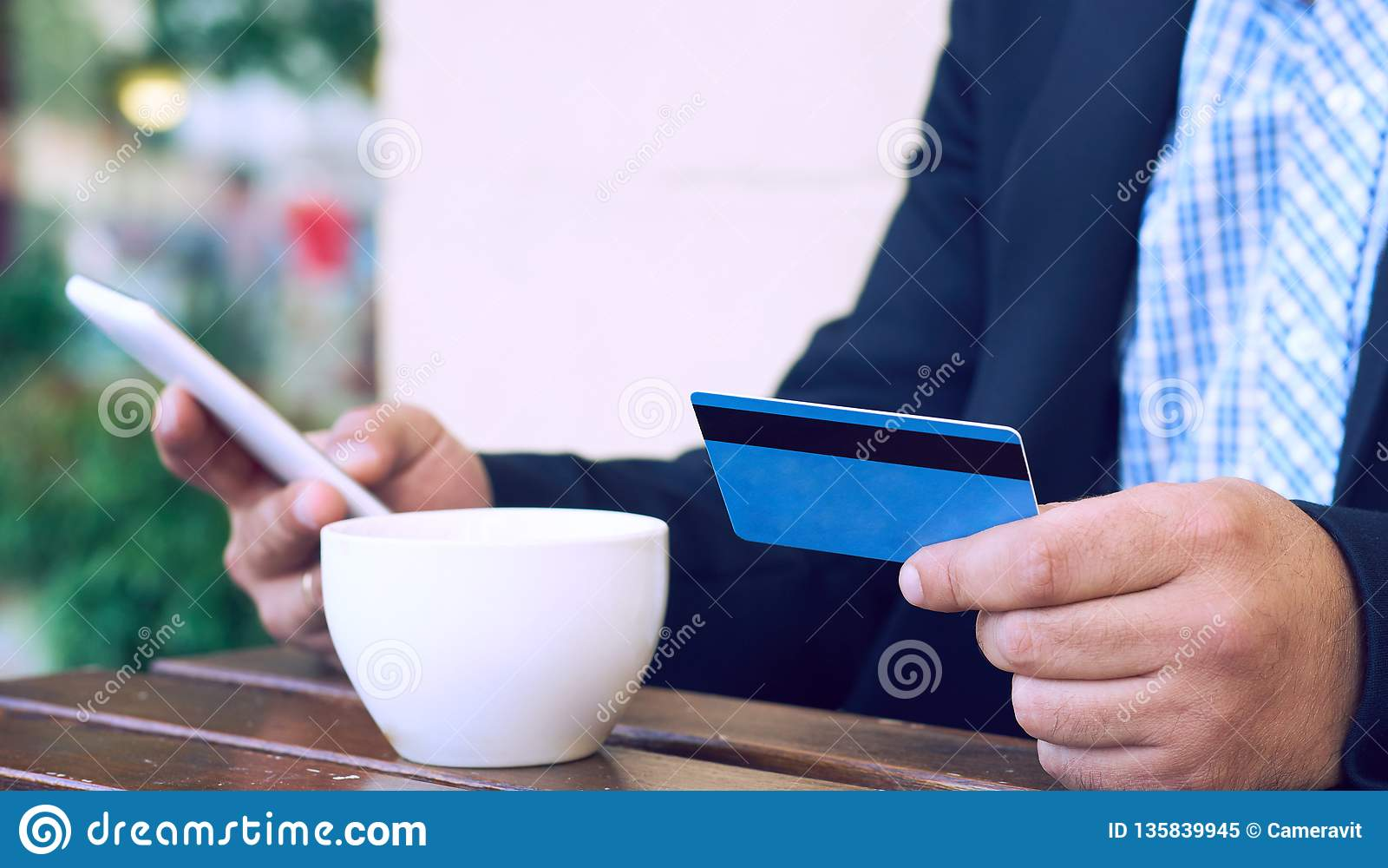 Internet banking, comércio eletrônico e conceito de troca em linha Ideia colhida das mãos do homem de negócios que guardam o tele