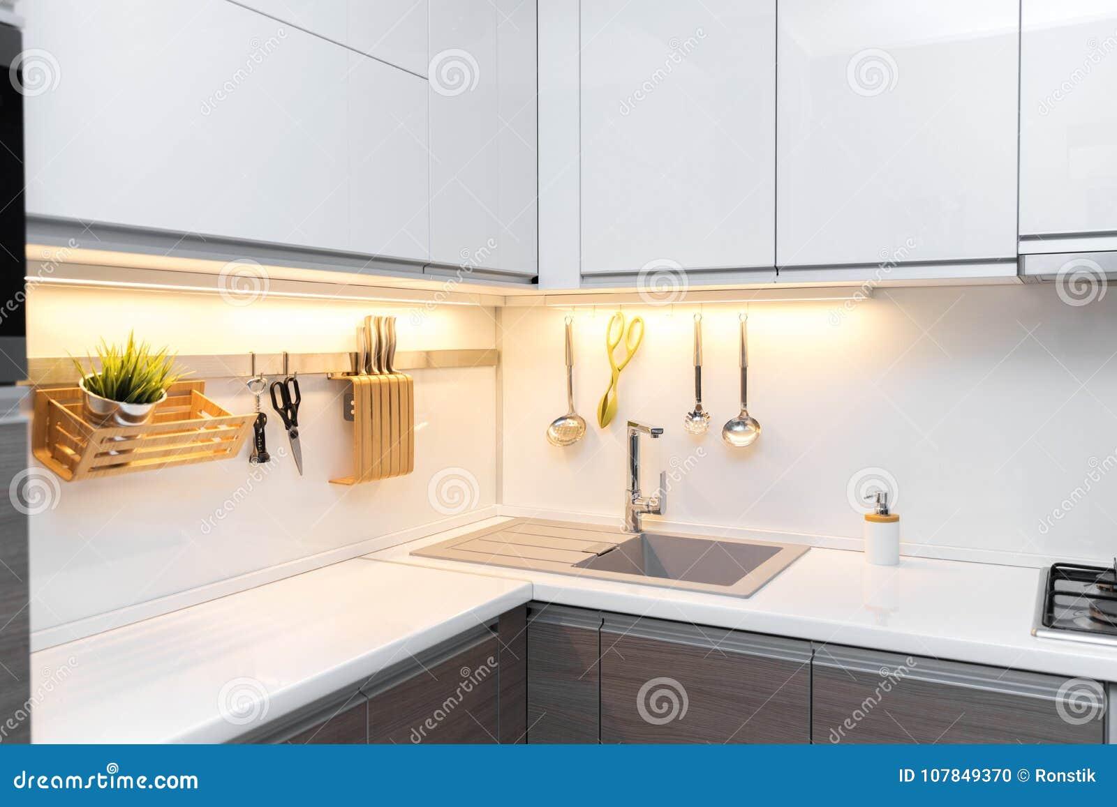 Interno bianco della cucina di lucentezza con illuminazione di