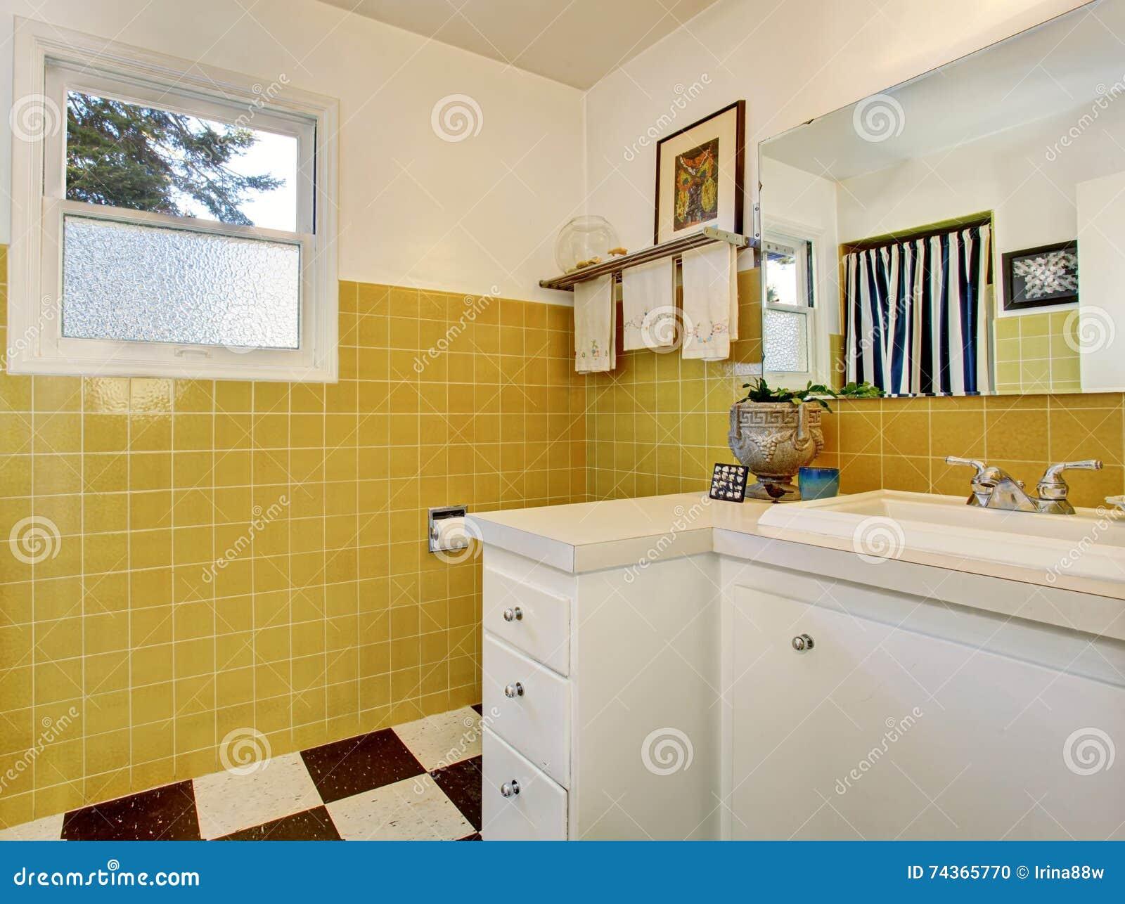 Interno del bagno con il gabinetto bianco le mattonelle gialle