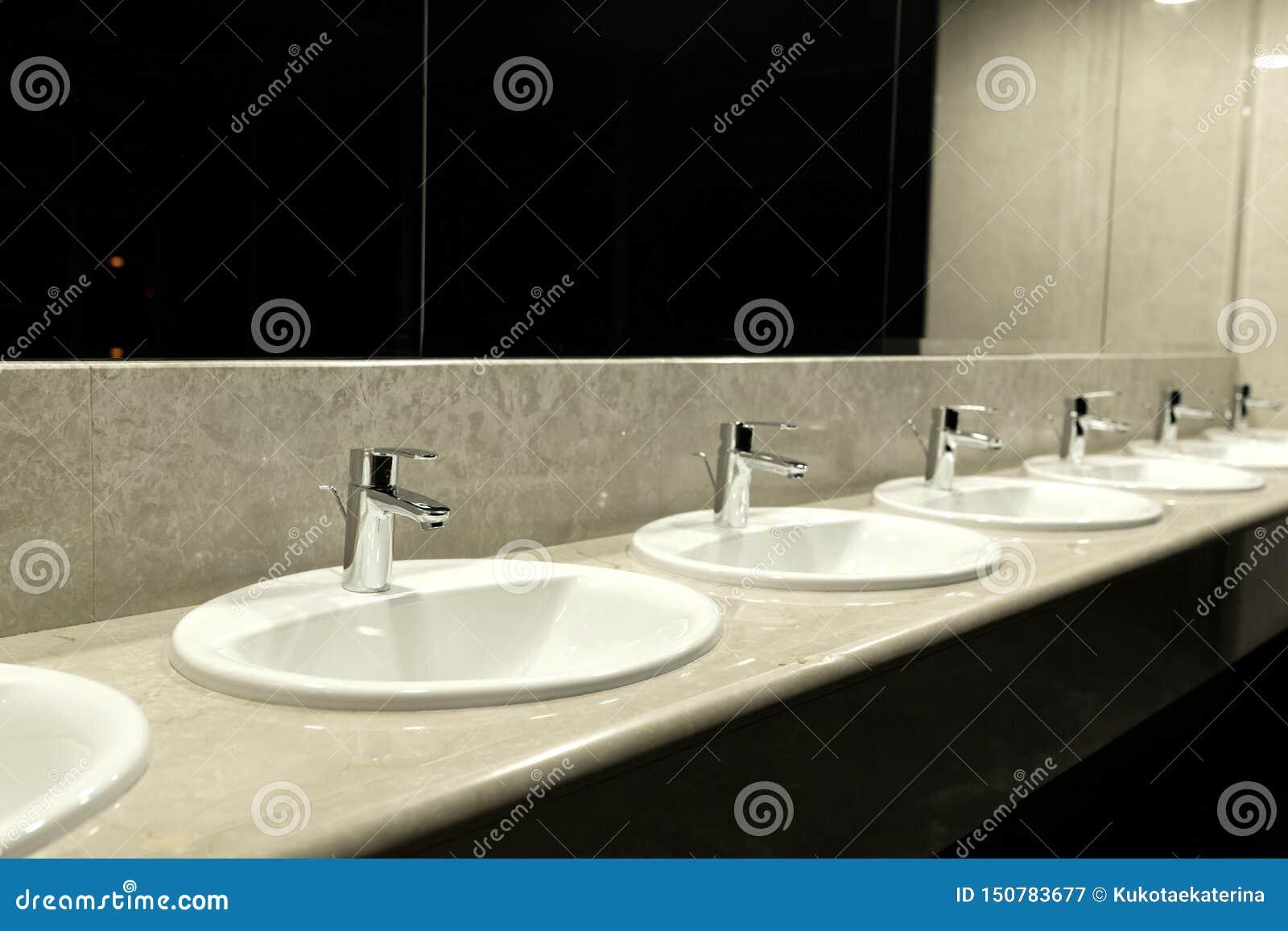 Interno del bagno e della toilette pubblica con il lavabo Rubinetti con dei lavandini nella stanza della toilette pubblica Lavand