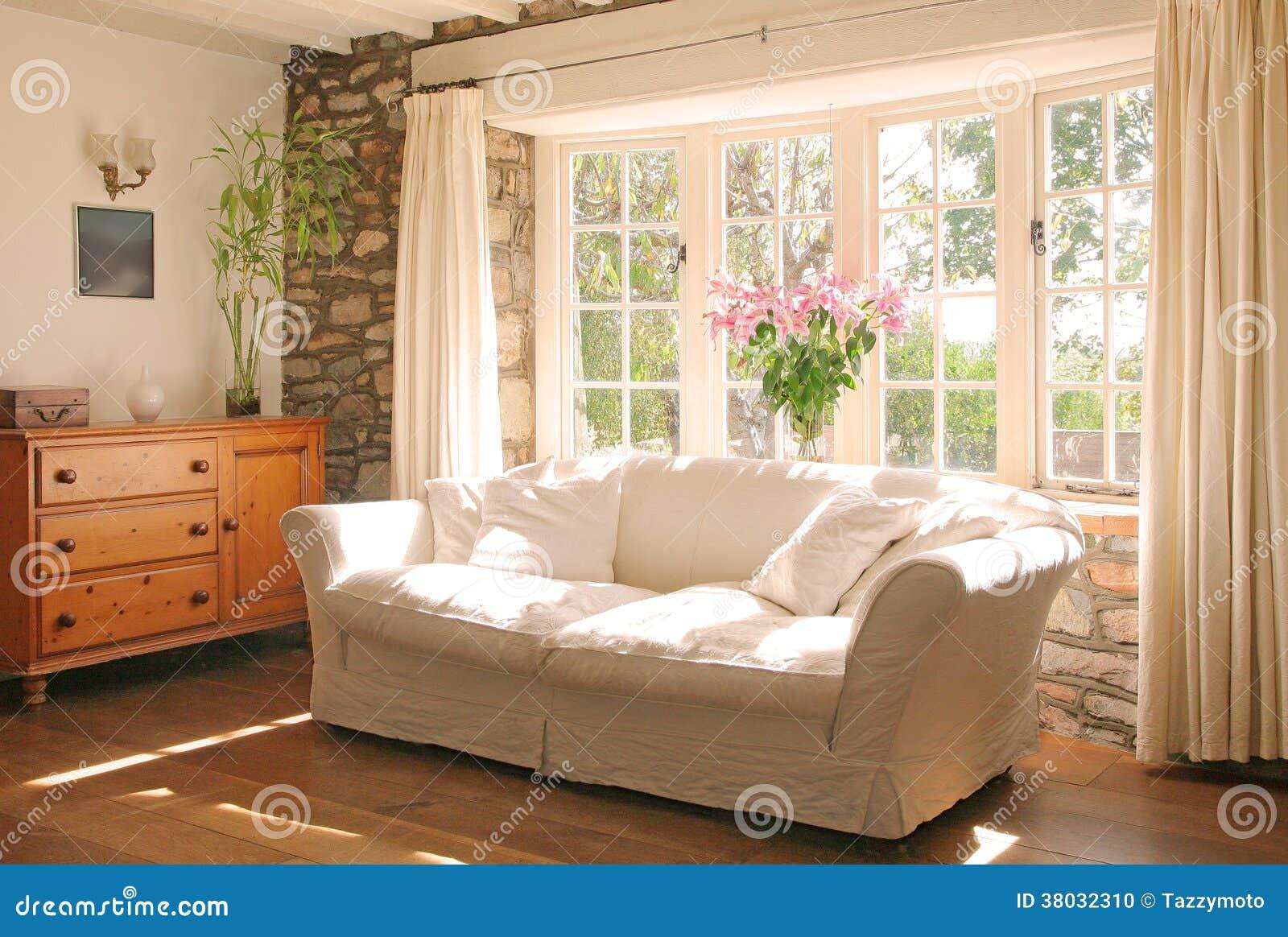Salone luminoso spazioso con la parete di vetro ed il camino del ...
