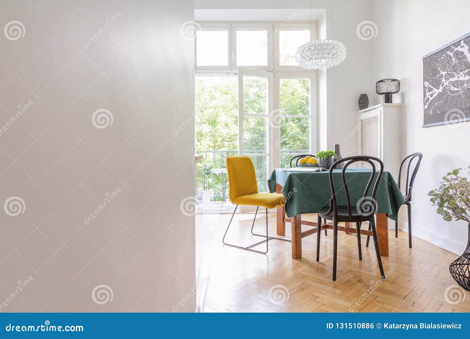 Interno del salone con la tovaglia e genere differente di sedie, mappa nera sulla parete, foto reale con