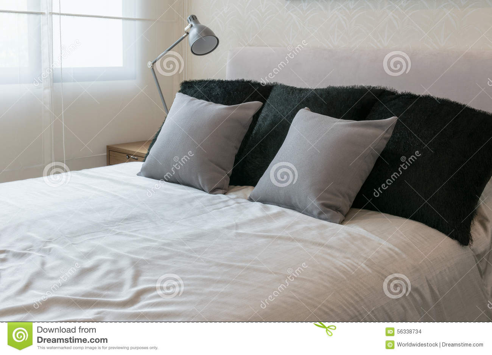 Interno della camera da letto con i cuscini grigi sul letto bianco fotografia stock immagine - Cuscini da letto ...