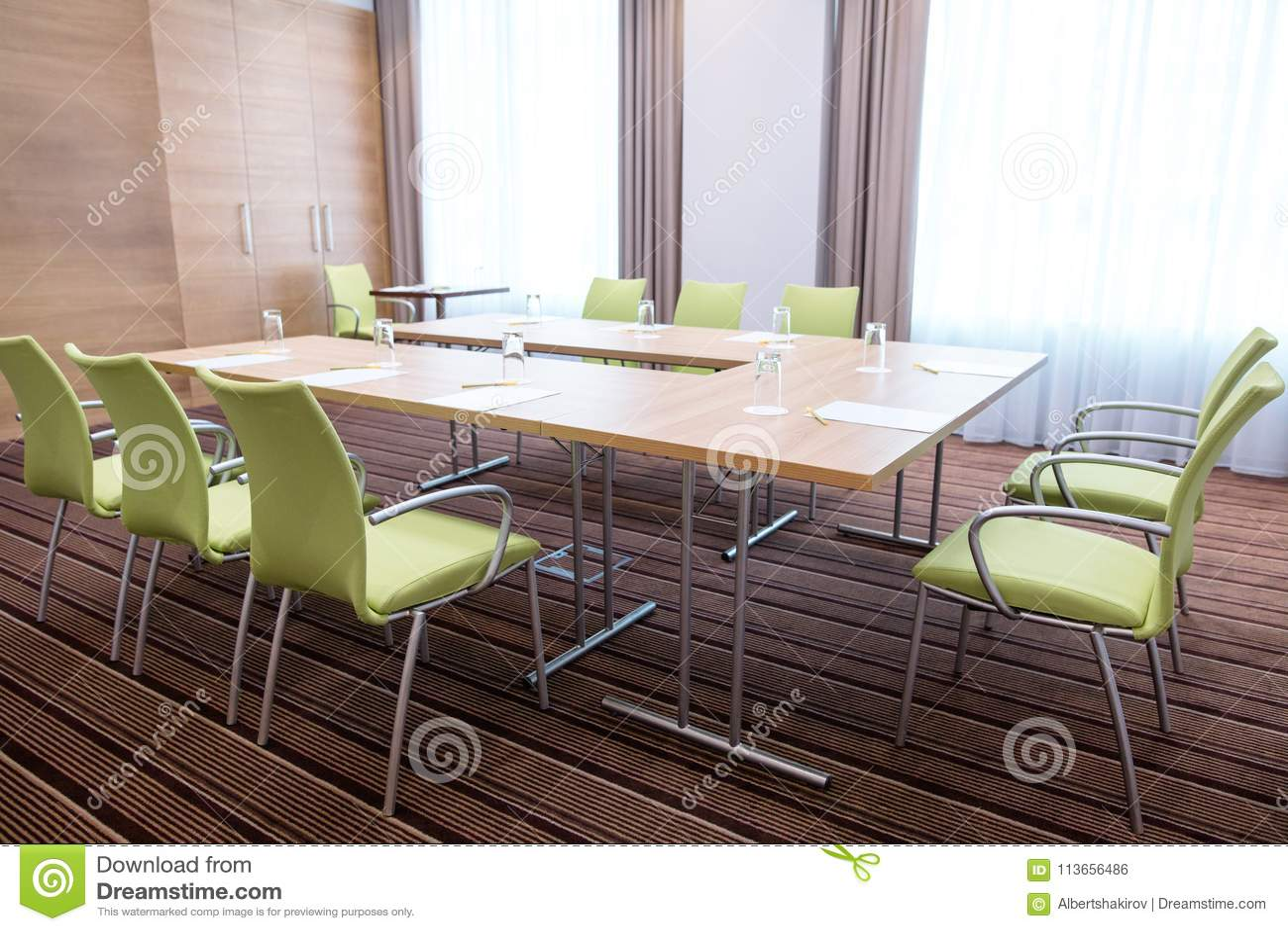 Interno di sala riunioni leggera ammobiliato di tavola moderna e di sedie verdi