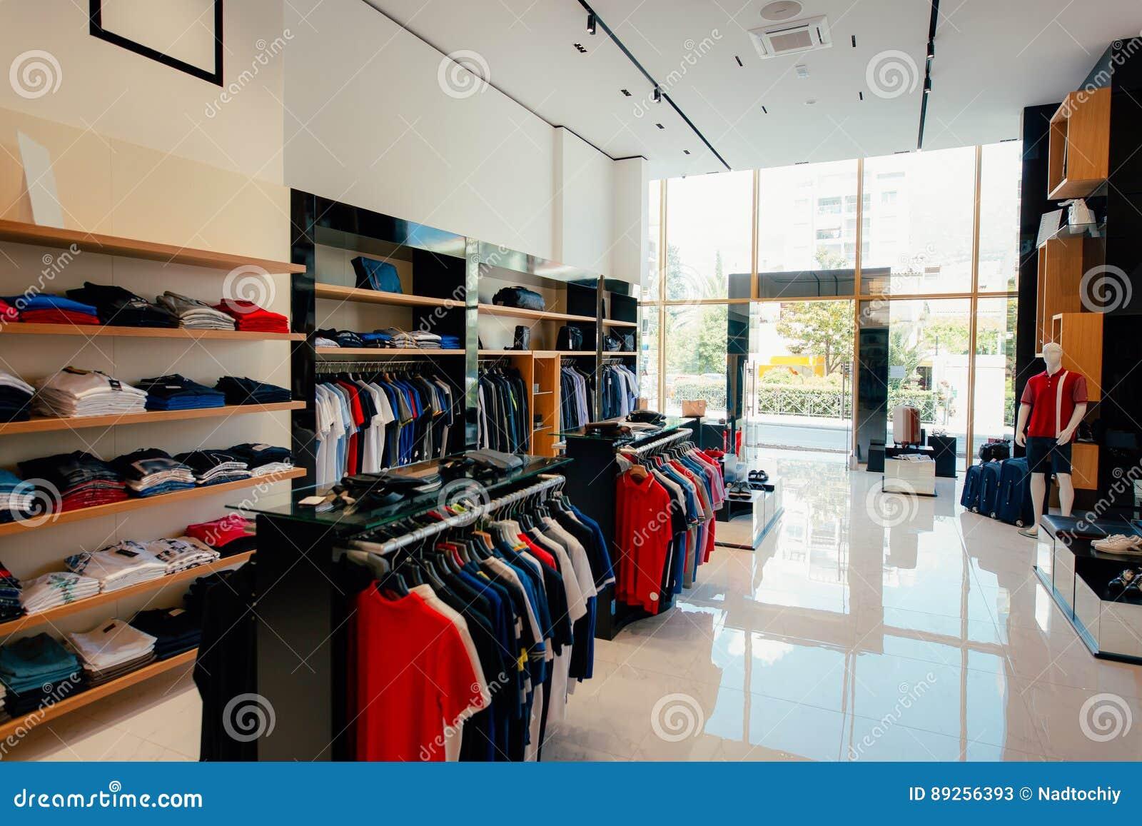 5b9a6184214f Interno di un negozio di vestiti Abbigliamento per gli uomini e le donne  sugli scaffali di negozio Negozio di vestiti dell estremità del corridoio di  ...