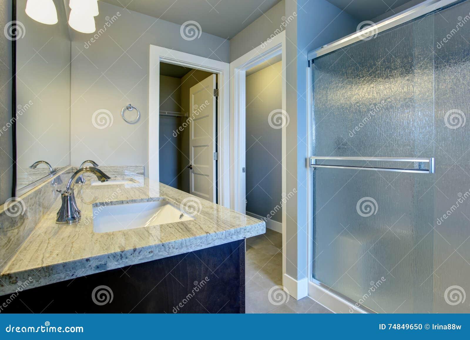 Interno luminoso del bagno con la doccia e la pavimentazione in