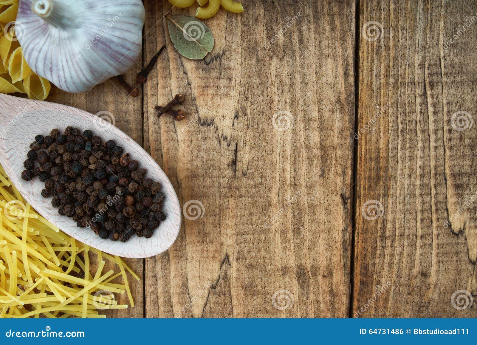 Intero pepe nero sul cucchiaio, sulla pasta e sull aglio di legno
