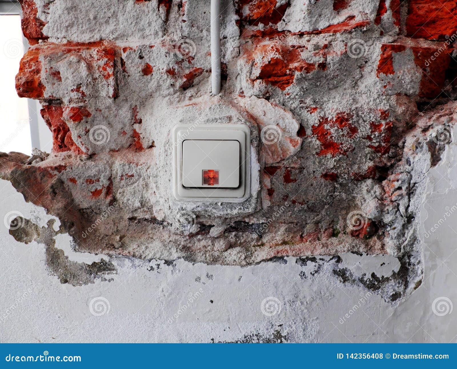 Interruptor da luz em uma parede com emplastro removido e os tijolos visíveis