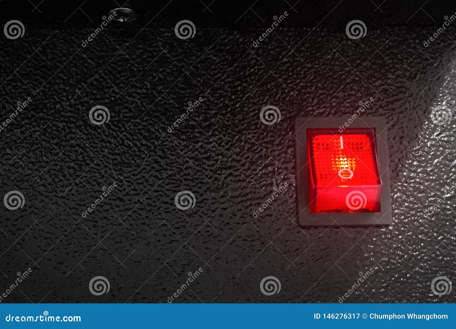 Interruptor de alimentação vermelho no fundo escuro Botão do controle elétrico