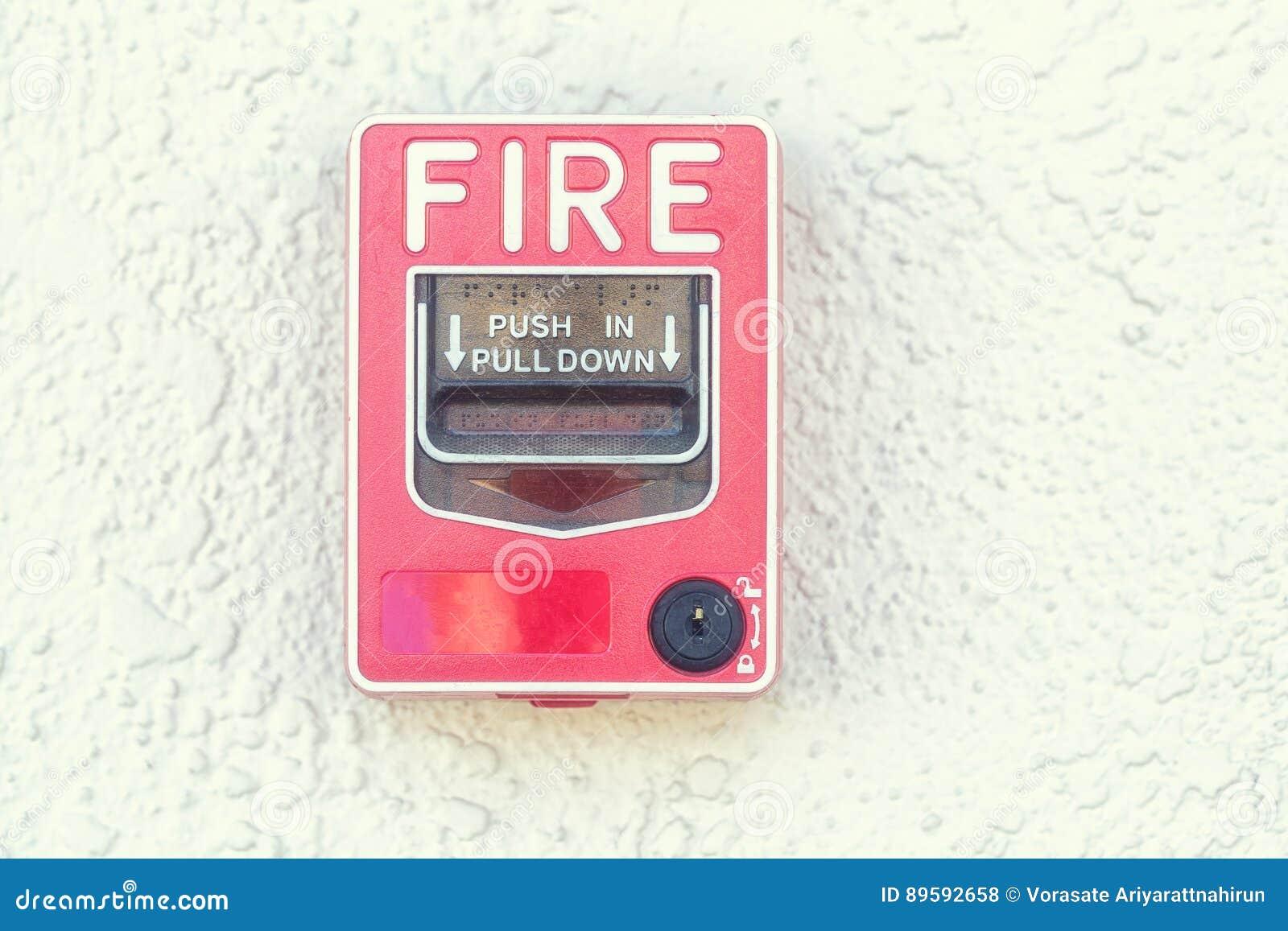 Interruptor vermelho do alarme de incêndio na parede do cimento