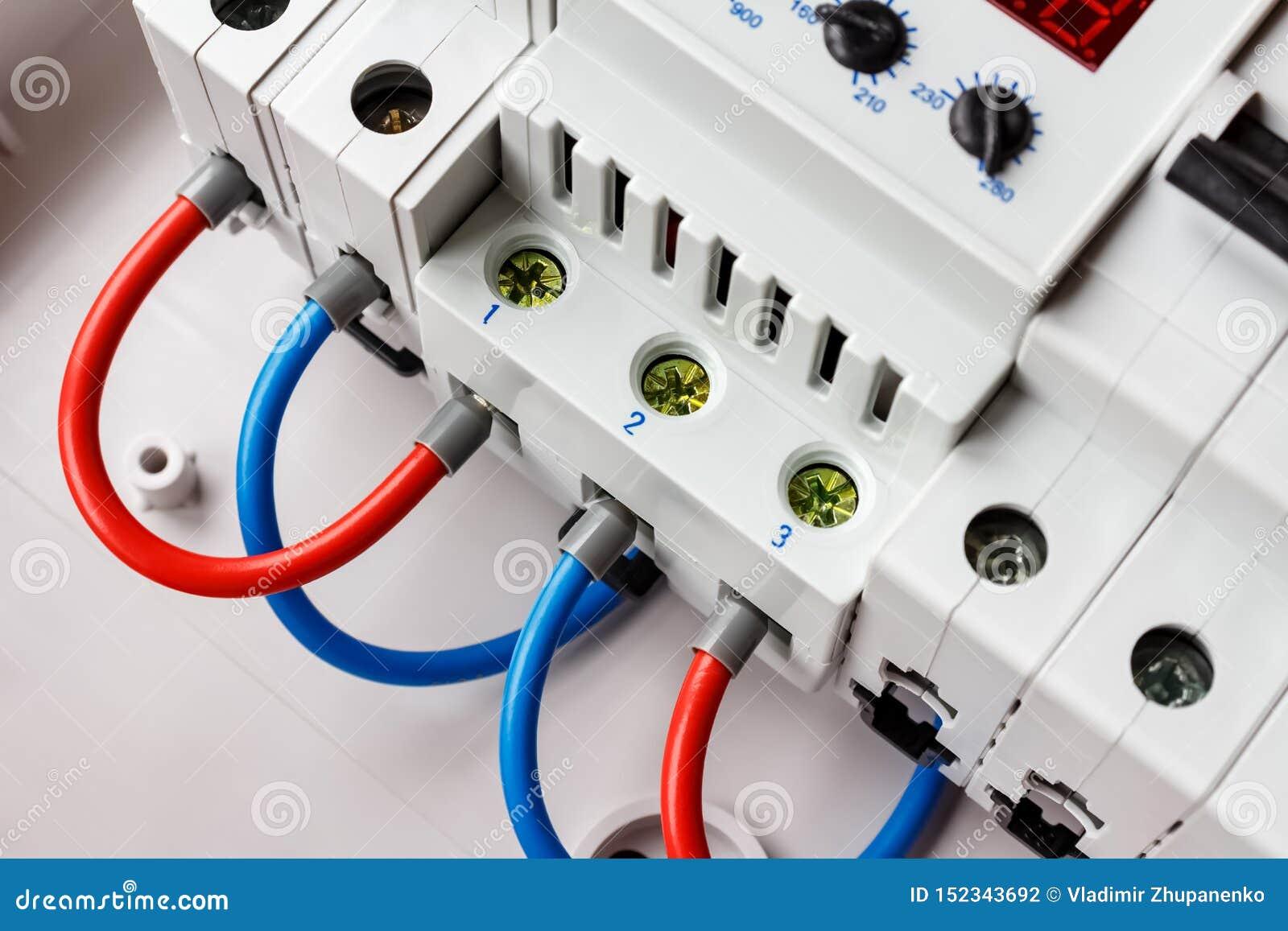 Interruptores automáticos e limitador da tensão conectado pelo close up vermelho e azul dos fios na caixa de montagem plástica br