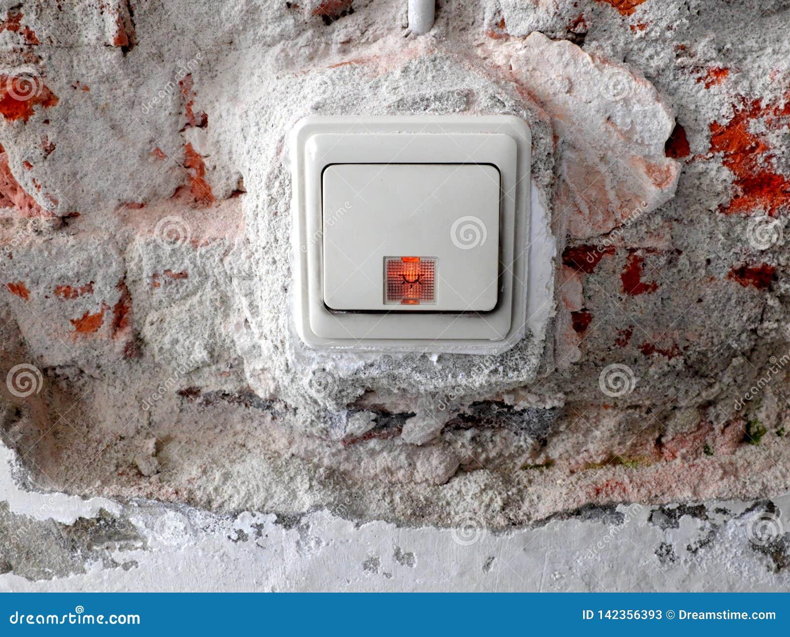 Interruttore della luce in una parete con gesso rimosso ed i mattoni visibili