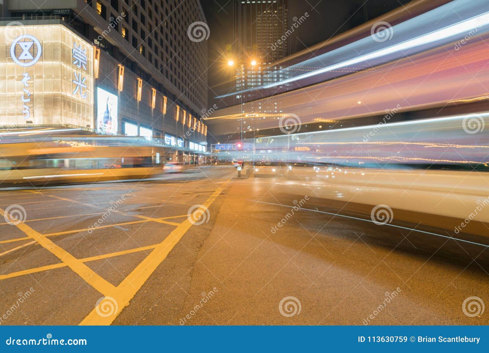 A interseção da cidade sob a noite ilumina-se enquanto os carros e os ônibus passam em z