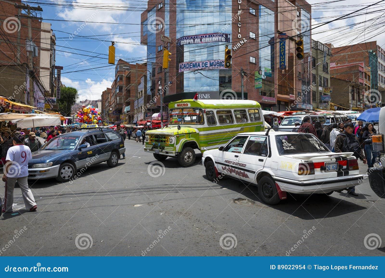 Interseção ocupada com carros, ônibus e povos na cidade de La Paz, em Bolívia