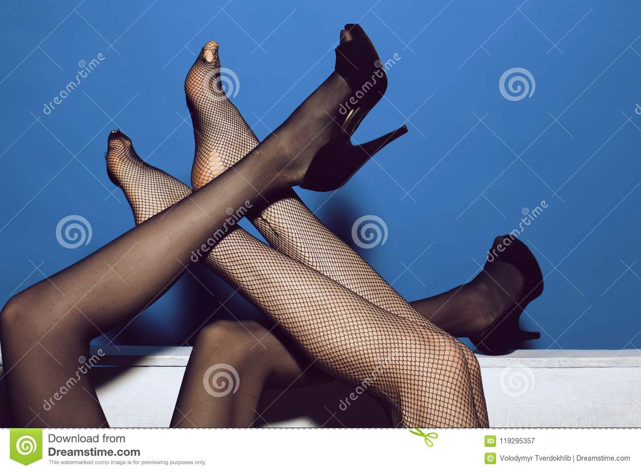 Intertwined Female Feet Legs Of Women In Fashionable Tights And Shoes