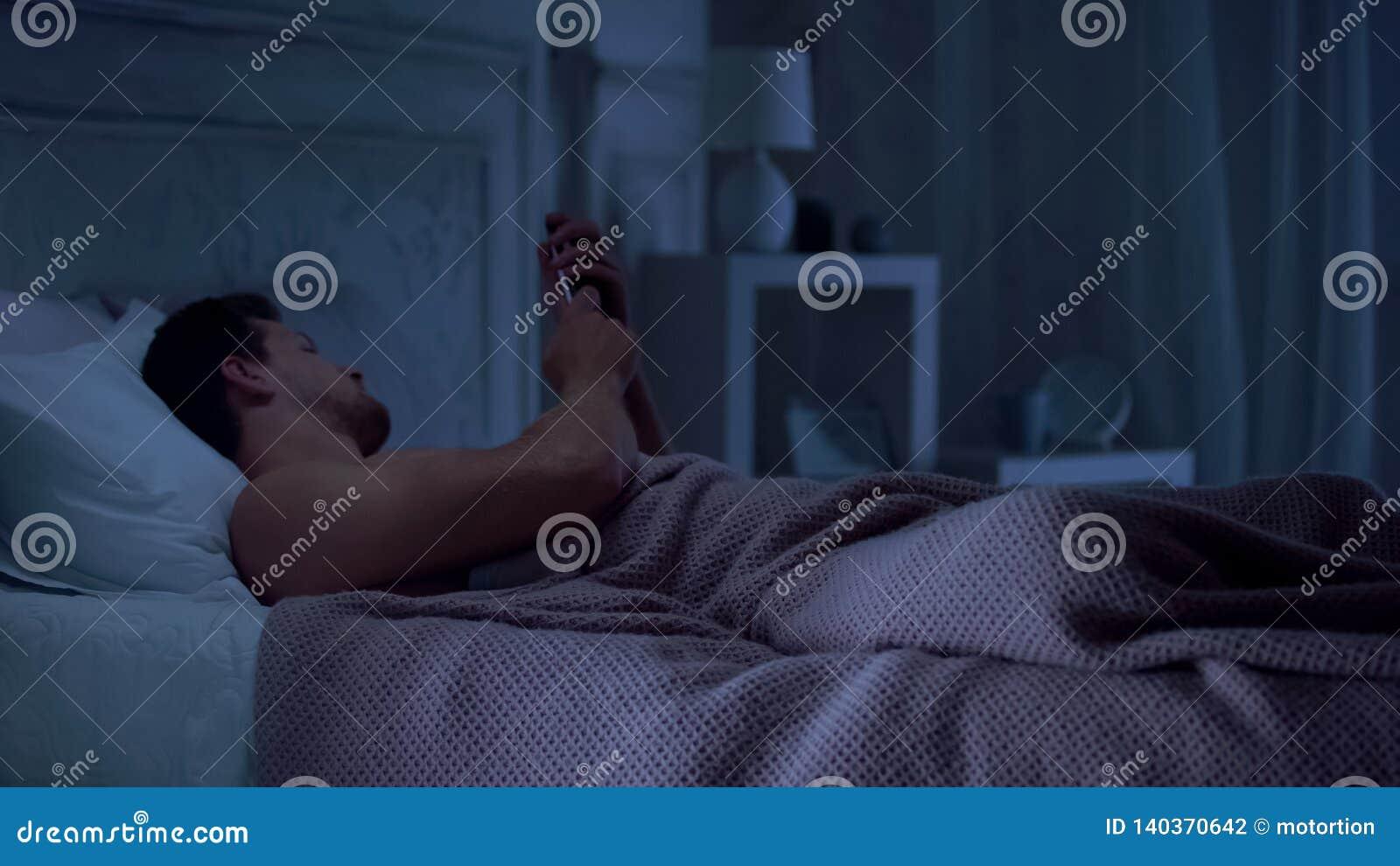 Intoxiqué de téléphone portable se situant dans le lit et causant sur le smartphone au lieu du sommeil