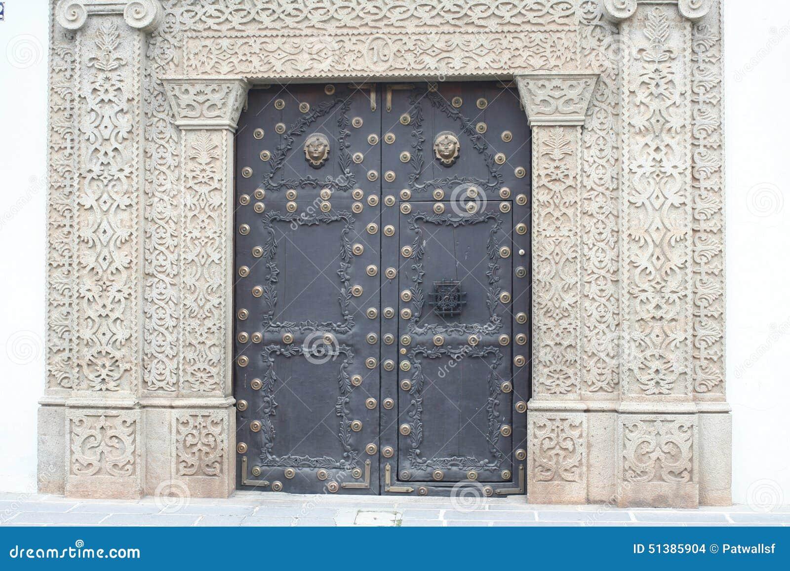 Big Metal Door : Intricate stonework frames large metal door in antigua