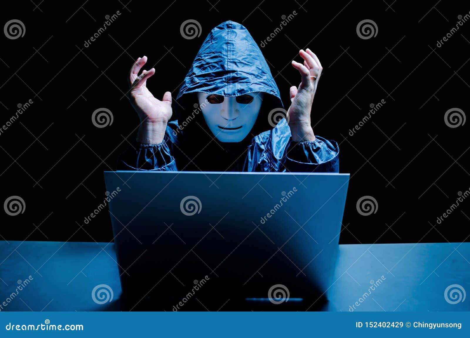 Intru anonyme dans le masque et le hoodie blancs Pirate informatique masculin stressant criant sur un ordinateur portable endomma