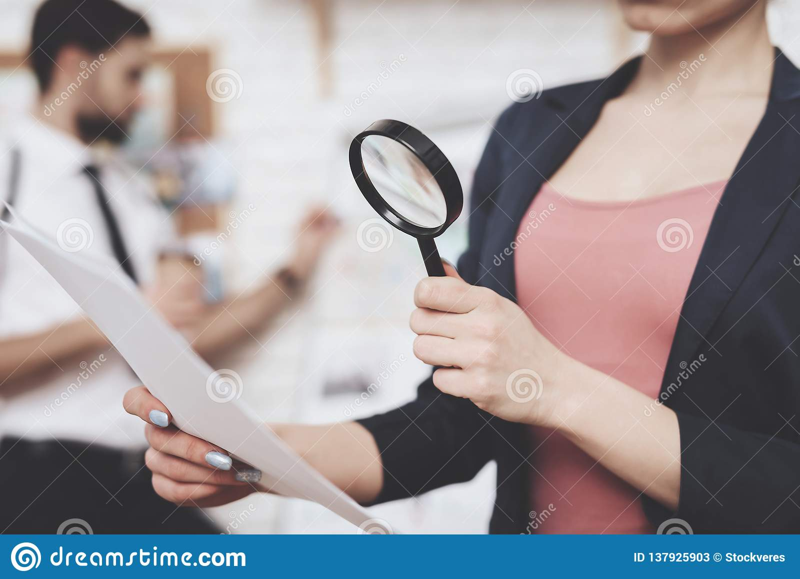 Intymna detektywistyczna agencja Kobieta pozuje z papierowym i powiększa - szkło, mężczyzna jest przyglądającym wskazówki mapą