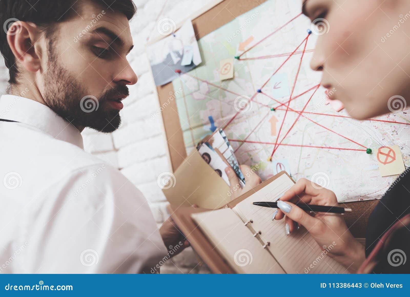 Intymna detektywistyczna agencja Mężczyzna i kobieta jesteśmy przyglądającym mapą, dyskutuje wskazówki