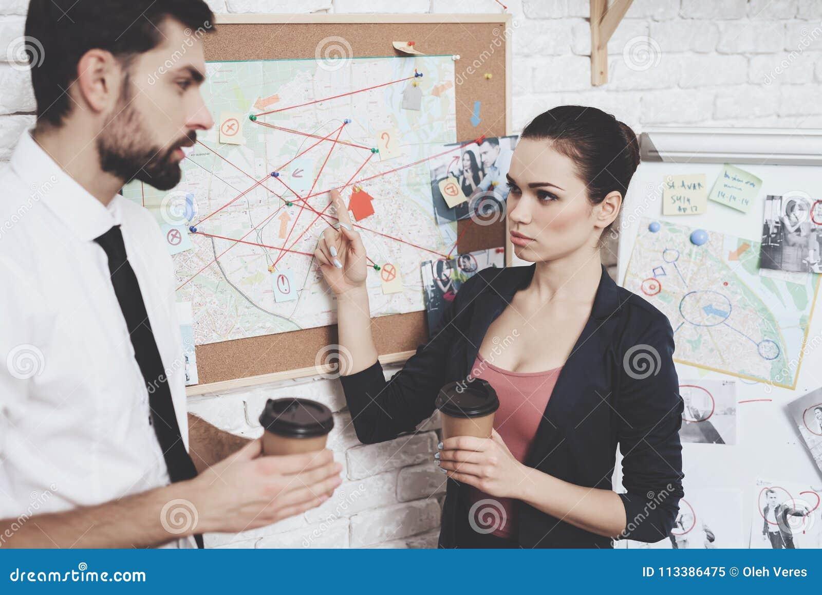 Intymna detektywistyczna agencja Mężczyzna i kobieta jesteśmy przyglądającym wskazówki mapą, pije kawę