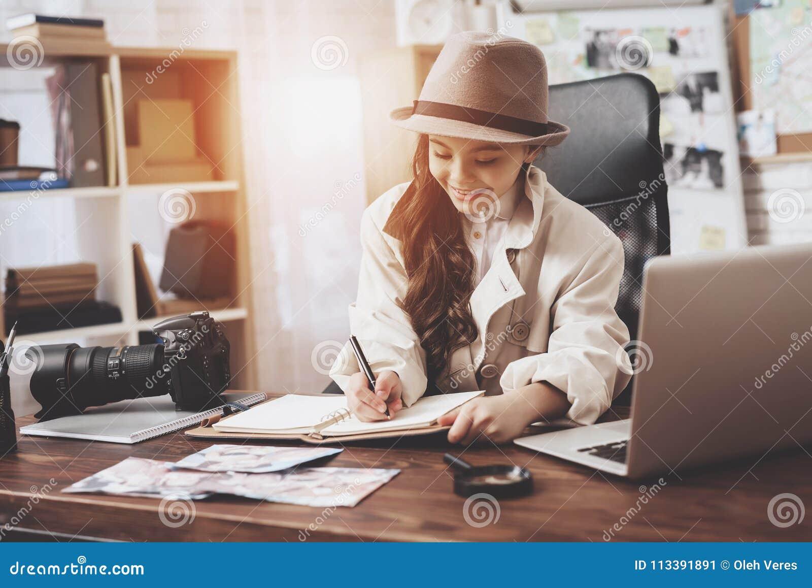 Intymna detektywistyczna agencja Mała dziewczynka siedzi przy biurkiem bierze notatki w notatniku