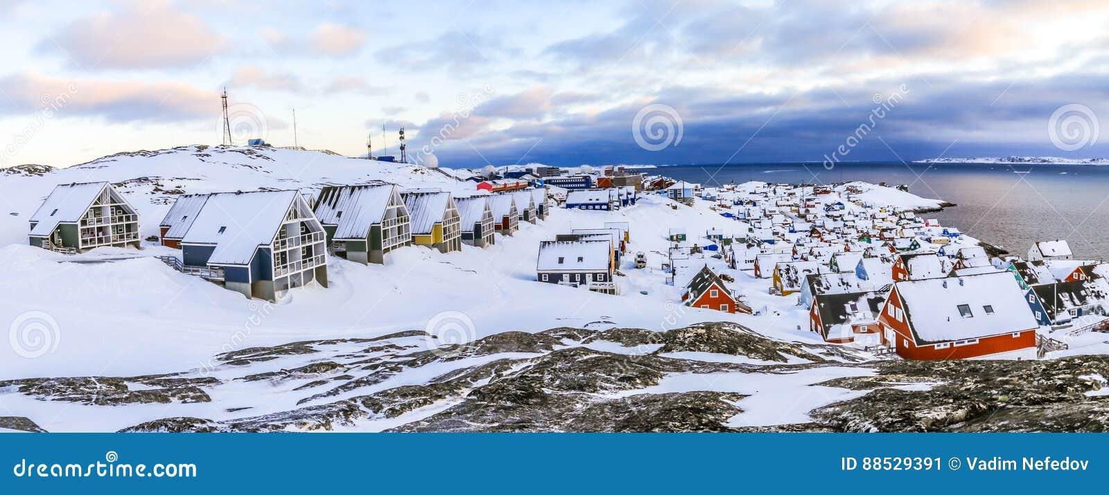 Inuithuizen in sneeuw worden behandeld die De lentepanorama van de Nuukstad, Greenla