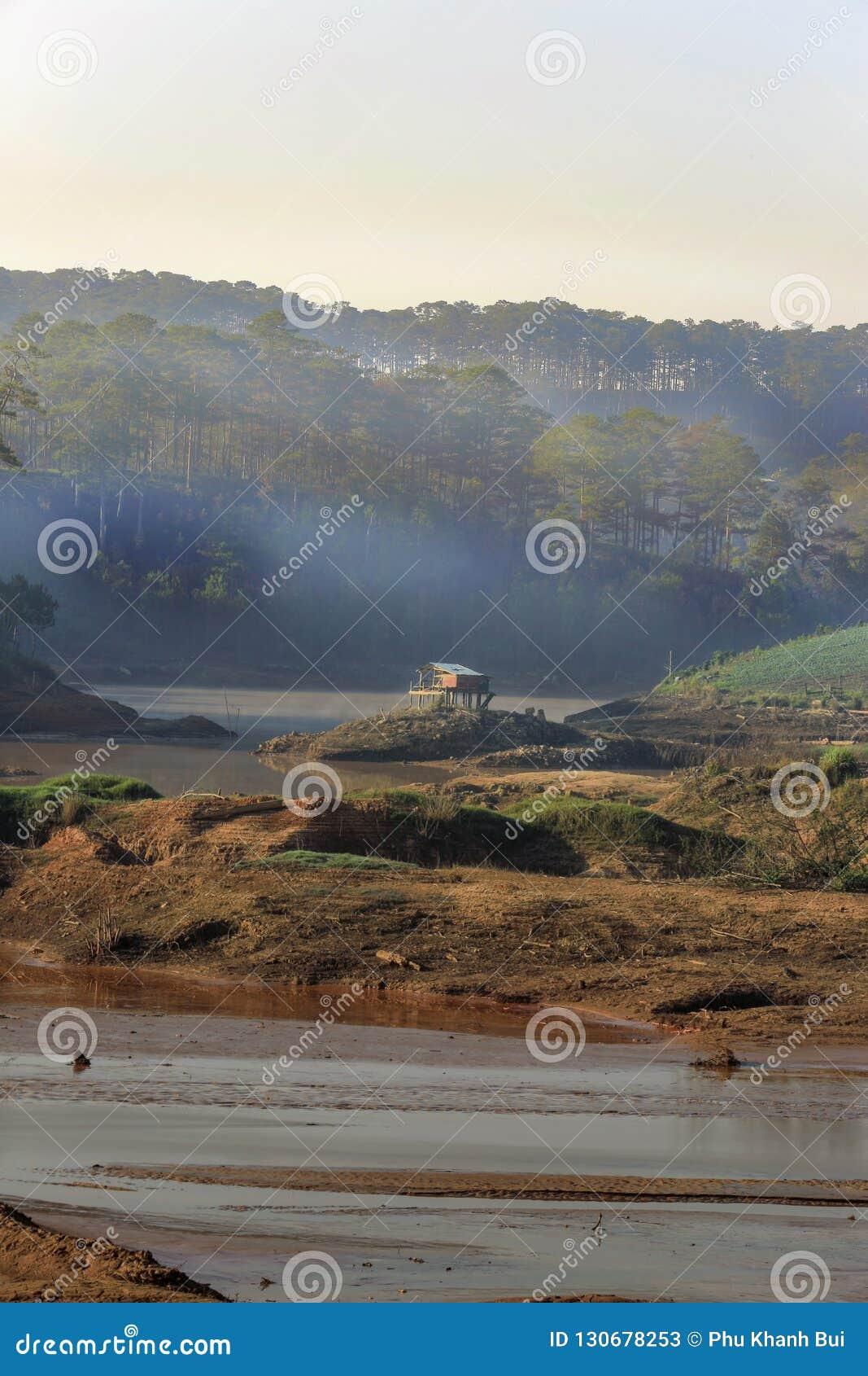 Inverkan av klimatförändring som göras torrt land, vattenbrister Ensamt litet hus mellan torra floder