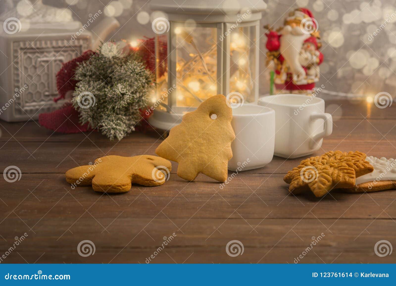 Inverno accogliente a casa con la bevanda ed i biscotti caldi Il Natale cronometra con tè e la ghirlanda