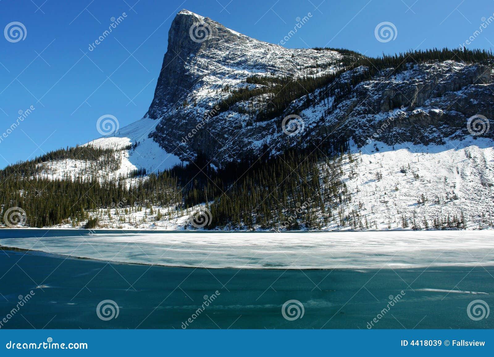 Inverno montagne rocciose e lago ghiacciato immagine stock for Cabine di pesca nel ghiaccio alberta