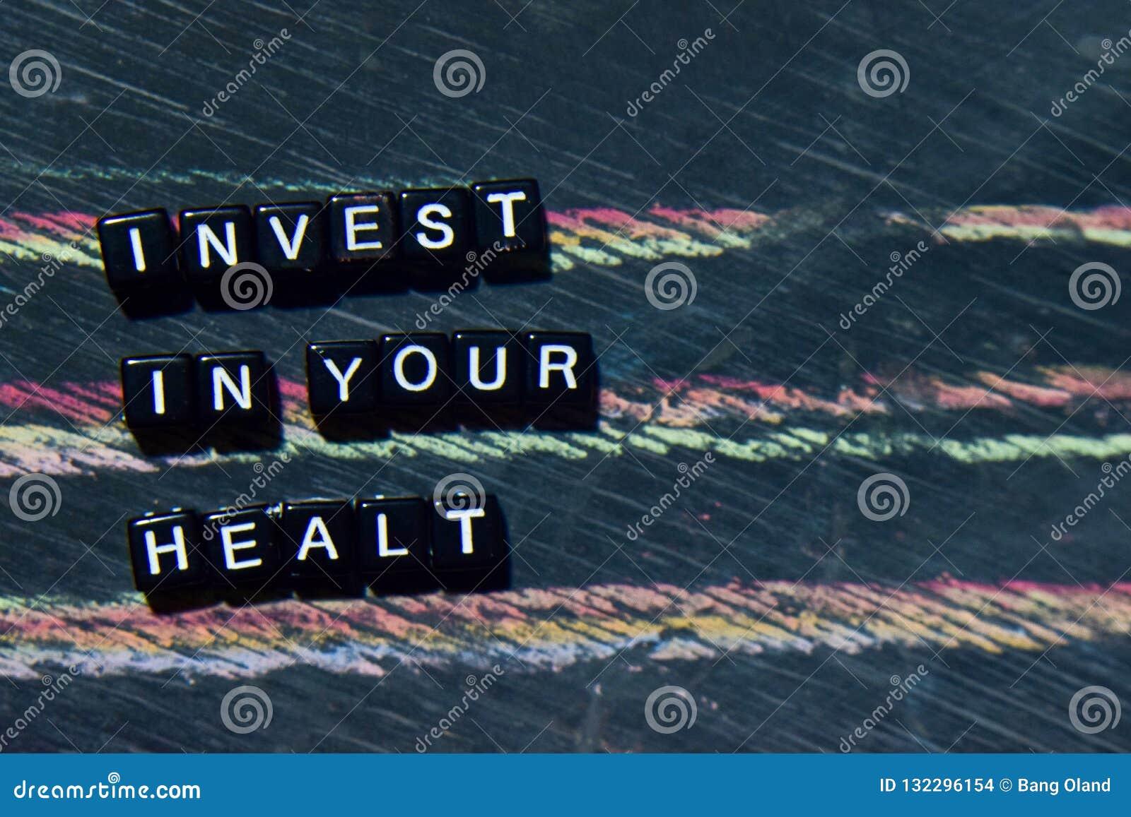 Investeer in Uw Gezondheid op houten blokken Kruis verwerkt beeld met bordachtergrond