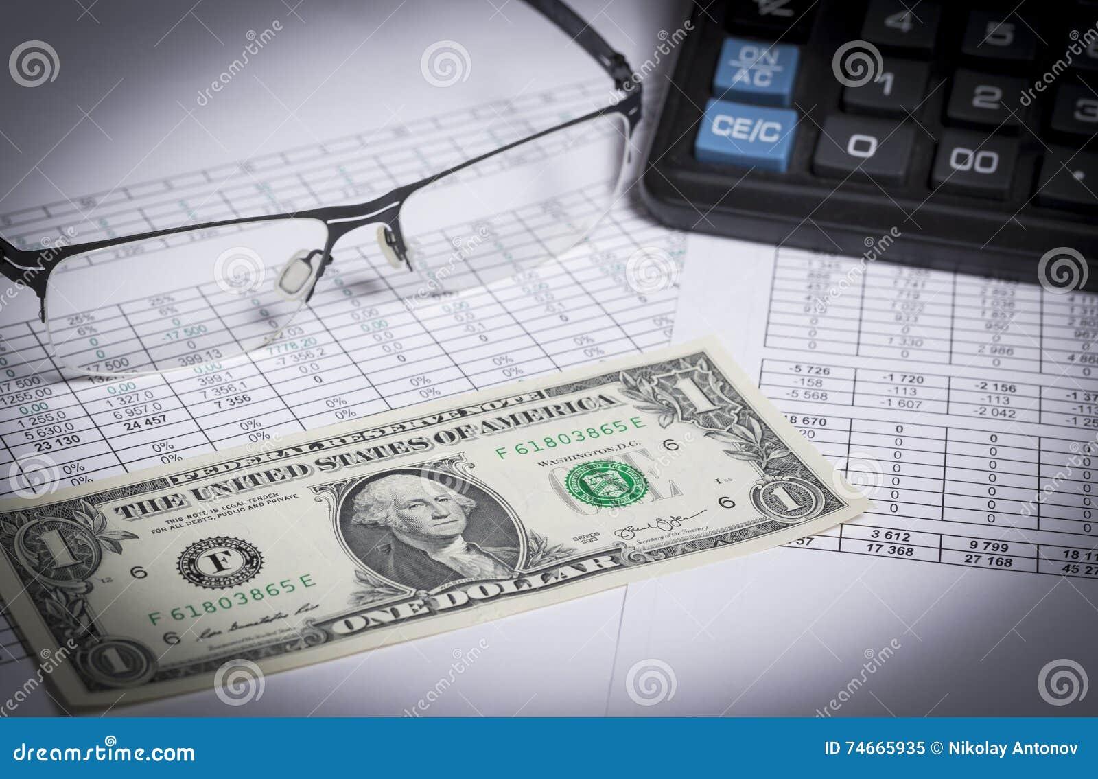 Investigación empresarial Primer de gafas, billete de dólar, calculadora en el papel con los dígitos