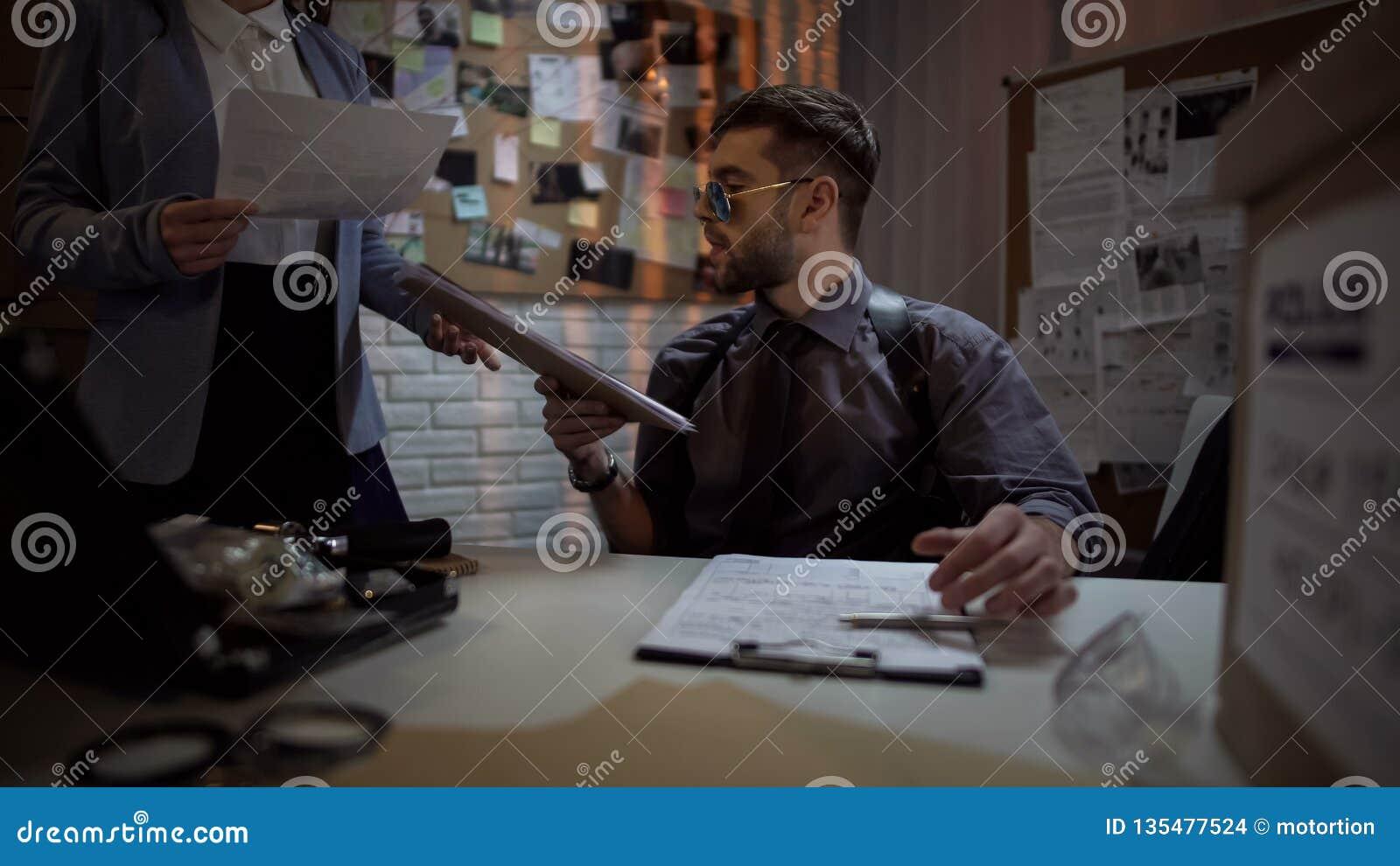 Investigador federal que mira a través de ficheros, caso complicado, pistas de la oficina