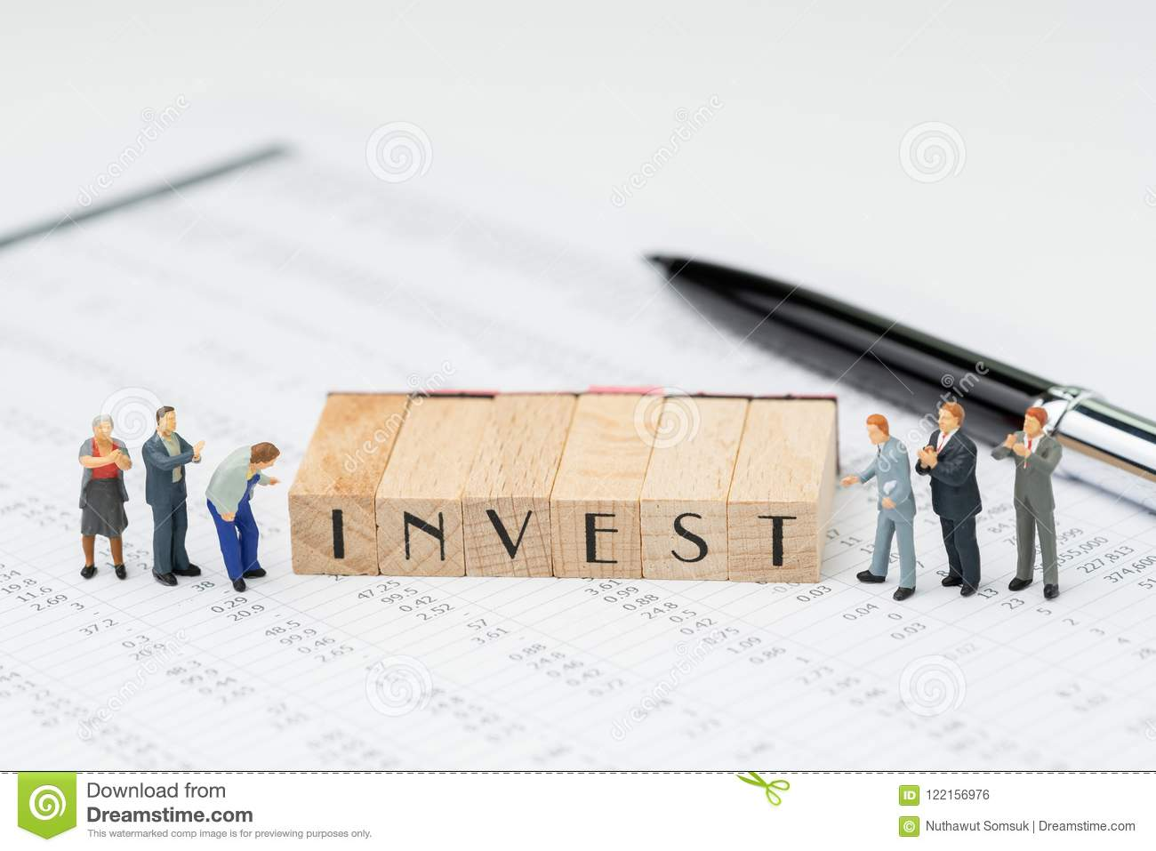 Investment concept, wooden stamp building the word INVEST with m
