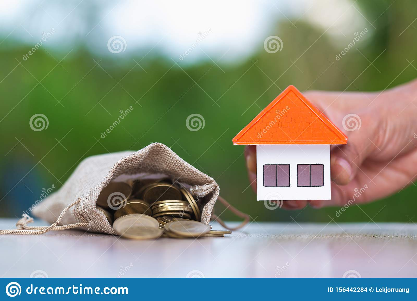 Investor show hand holding a model home , Saving money for buy a new house and loan for plan business investment for real estate