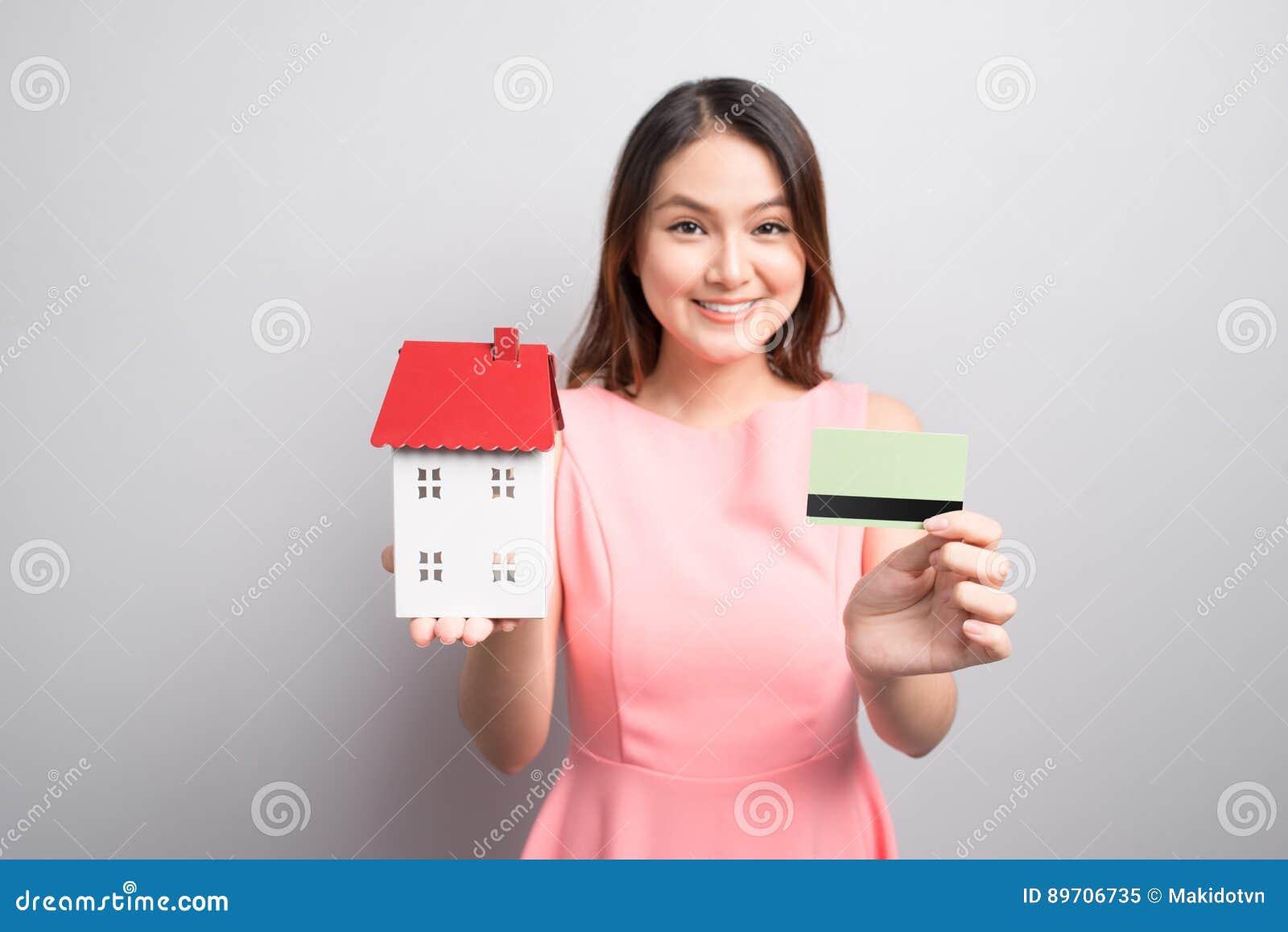 Invierta en concepto de las propiedades inmobiliarias Mujer que sostiene la pequeña casa del juguete y